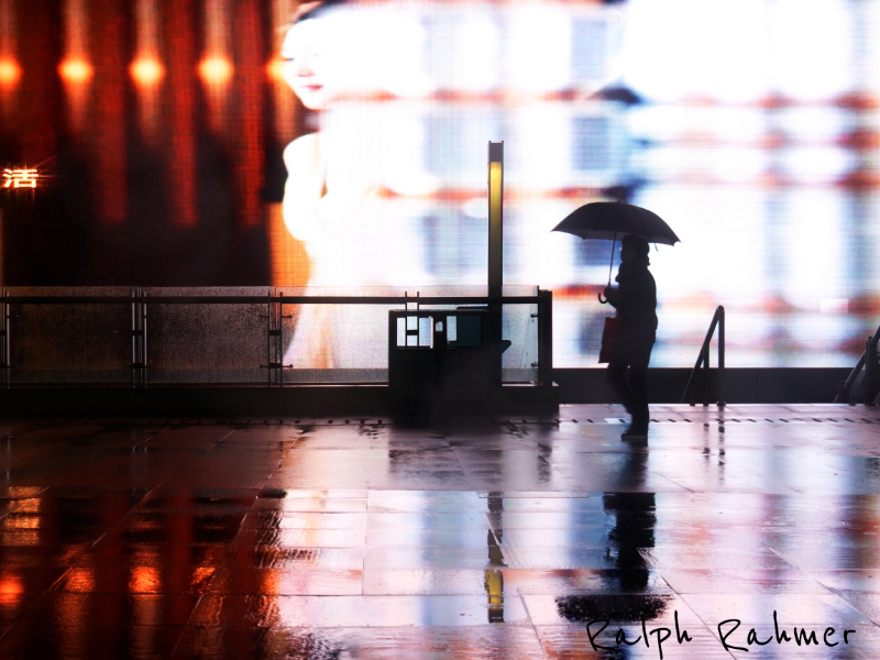 A person walking in the rain in front of of an oversized screen. The colours of the display are reflected on the wet floor and form an explorer colours and the person appears fragile against this