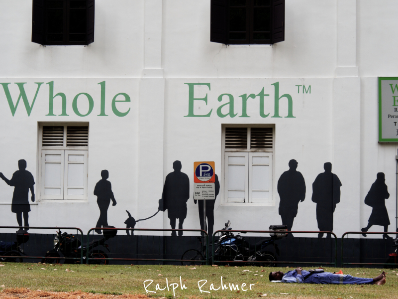 """A worker slumbers in front of a building on which silhouettes of moving people and the words """"Whole Earth"""" are painted"""