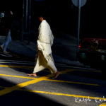 A high contrast photo of a Hindu monk walking across a street intersection