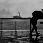 Gloomy black and white photo of a man walking along Hong Kong harbour on a cold, Romy, foggy morning