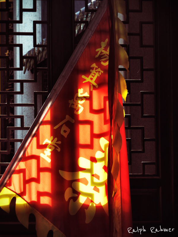 A red ornamented flag on the window of a temple, illuminated from behind and shadows of the window frames falling on it
