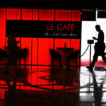 Silhouettes of two strangers encountering by chance in front of a Cafe. The picture has two distinct halves formed by the red glass front and the entrance of the Cafe with a clear window.