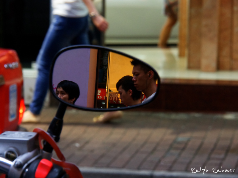 Photography of the mirror of a scooter showing people walking by. Passers on the other side in the background, Bokeh