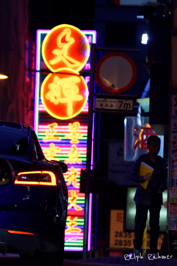 A photo showcasing the bright lights of Soho in central HK in the night. A man with a yellow binder and a car in the foreground