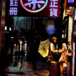 Two beautiful girls saying farewell in a brightly illuminated entrance in very heavy, dark rain, neon lights, Bladerunner athmosphere