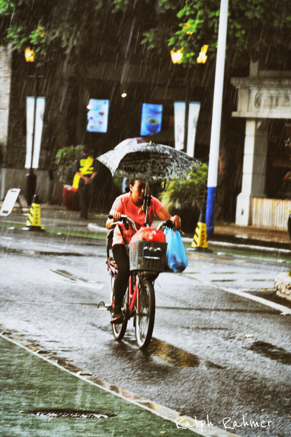 A woman cycling through heavy rain with an umbrella fixed to the bicycle. Her bright red shirt shirt stands out against the mute, rainy background