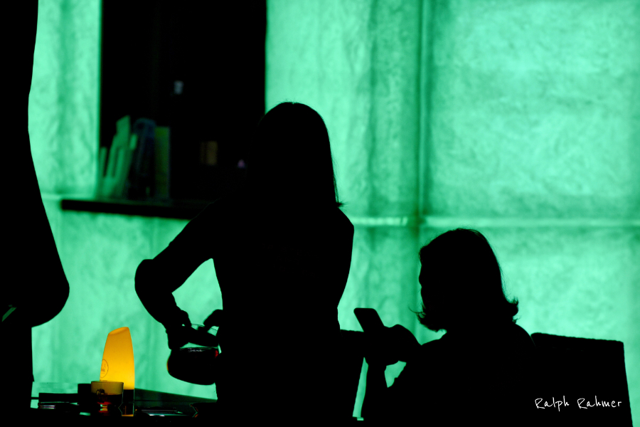 Night photography. Silhouettes of a patron and a waitress against brightly green illuminated background. An orange table provides a small colour contrast accent