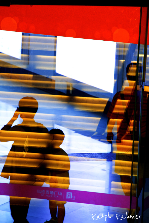 A glass door, the reflections flow together with the people behind and give a two dimensional effect