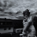 Humoristic black and white photo: A statue of Zeus in the parking lot of a Greek restaurant in a German town in the background storm clouds