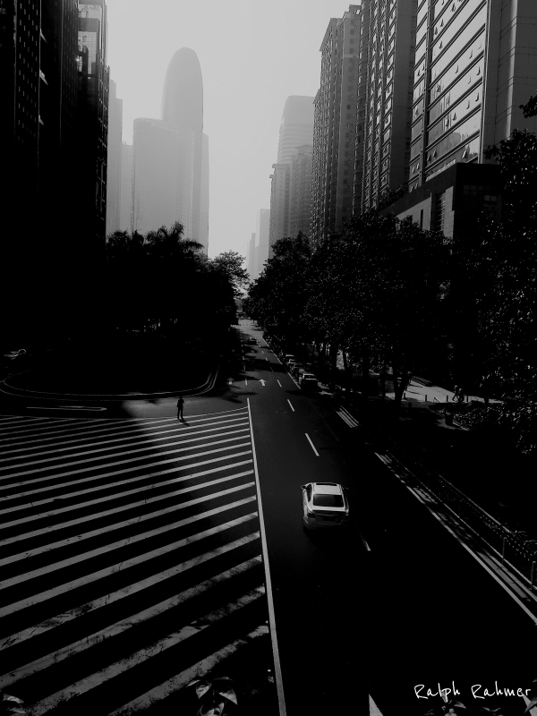 Black and white photography of a wide avenue and tall buildings with high contrast. A small solitary human silhouette crosses the street