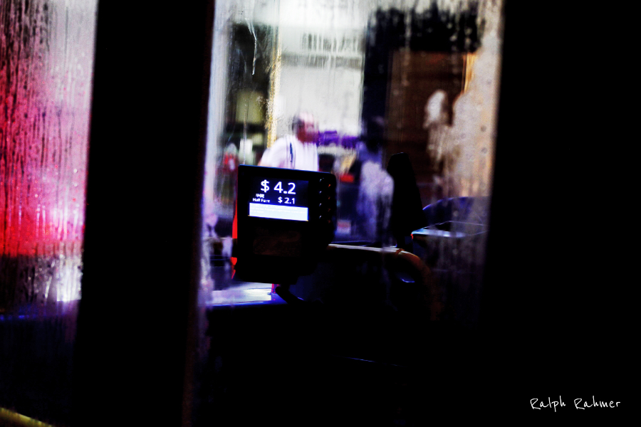 A picture shot through the entrance of a bus in the rain. The picture is focused on the ticketing machine. In the background people and city lights are visible but blurred through the bus front window