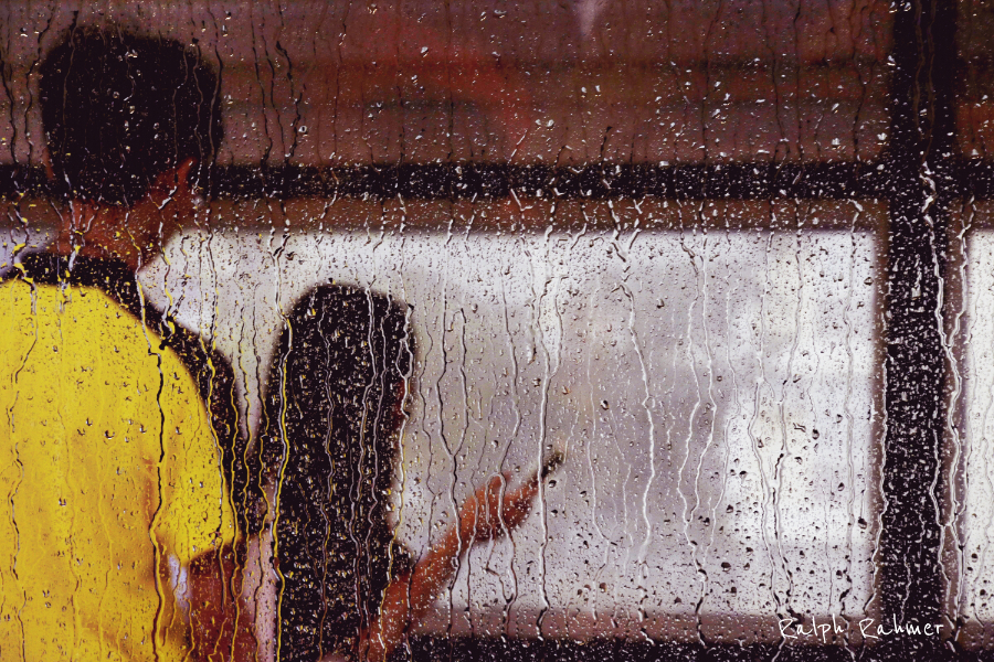 Looking out through a rainy metro train window on people at the station