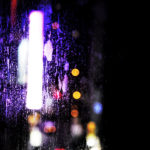 A damp hotel window in the night, in the background blurred, colourful city lights visible