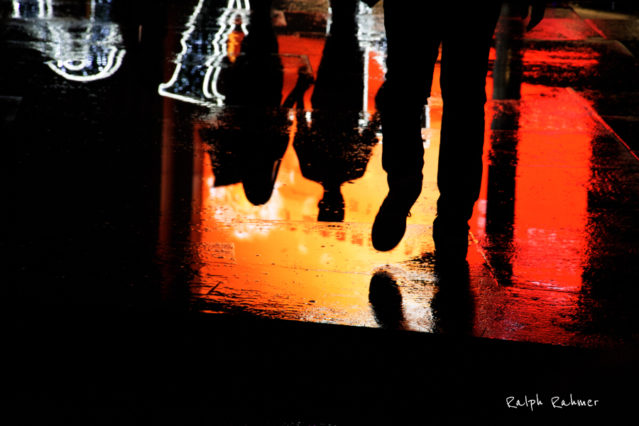 Urban photography showing the Silhouette of a man in front of the reflections on a rain pool of couple against red back background