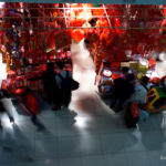 A slow shutter photo of people shopping for Lunar New Year decorations in a mall