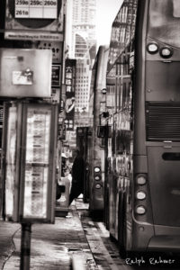 A black and white picture showing a man exiting a bus in Mongkok