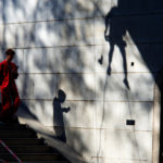 A man in red contrasted with the shadow of a worker hanging from the roof