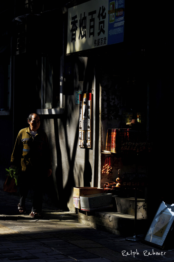 Photography of a street scene in Guangzhou's old town. A man passes a shop. Harsh contrasts of a tree falling over the scene, mysterious athmosphere