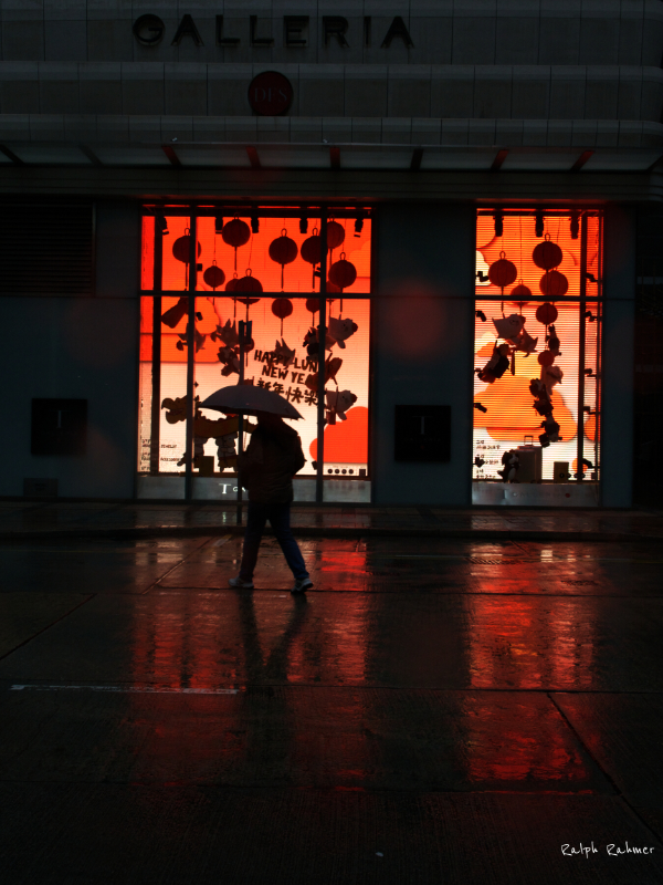 A man walks through the rain in front of a shop window decorated for Chinese New Year