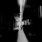 Black and white photography of a narrow alley in backlight. With high contrasts. The light appears cross shaped. Outlines of people visible