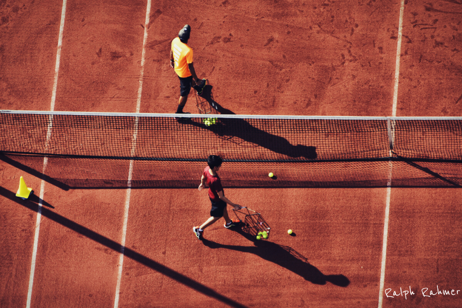 Two tennis court clerks moving in parallel along the net of a tennis court and collecting left balls