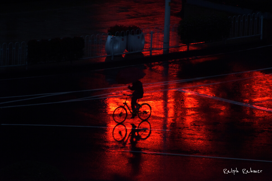Night photography, man on a bicycle in the rain, the wet asphalt reflects intense red light