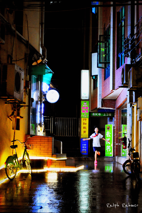Night Photography of an alley with colourful lights, reflected on the pavement and a child running out in joy in the warm rain