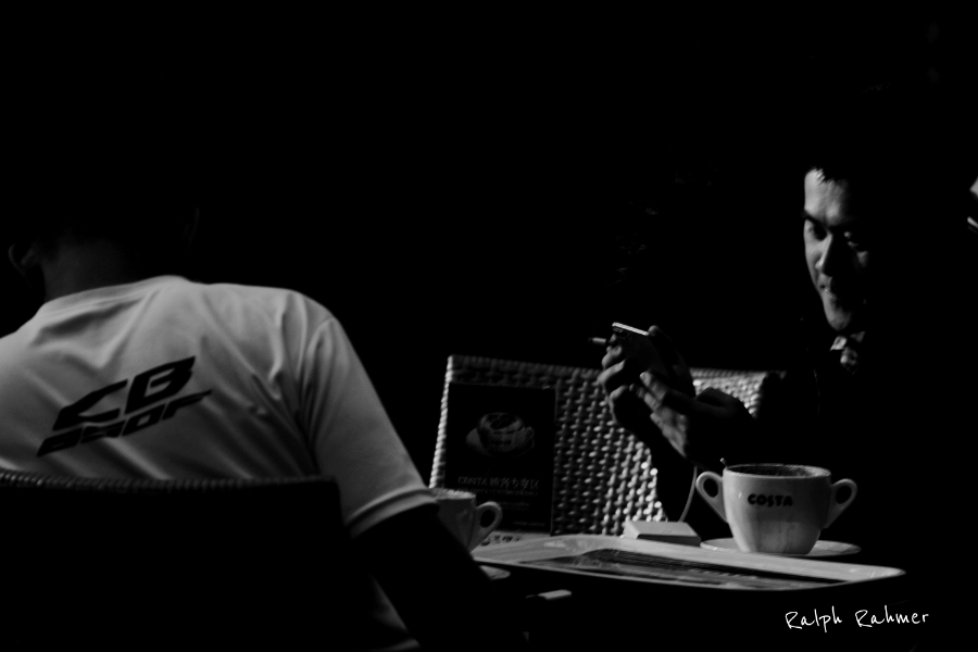 A black and white photo of two men in a cafe with harsh contrasts, film noire style