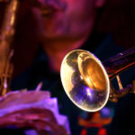 In the foreground trumpet of a jazz player, in the background the saxophone player