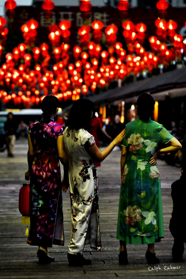 Three ladies in Traditional Chinese dress in a street with red lanterns
