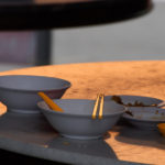 Table with left dishes and chopsticks in the afternoon sun