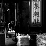 Black and white photo with harsh contrasts os a street in Hongkong with TCM shops