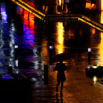 A street scene in the rain with colourful reflections on the wet street