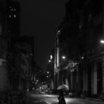 Black and white photo of a lady crossing a street in the night in the rain
