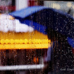 Lights of a cruise ship and a person with an umbrella seen through a rainy window