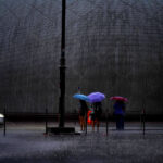 People with colourful umbrellas in a heavy rain in front of HK Space Museum